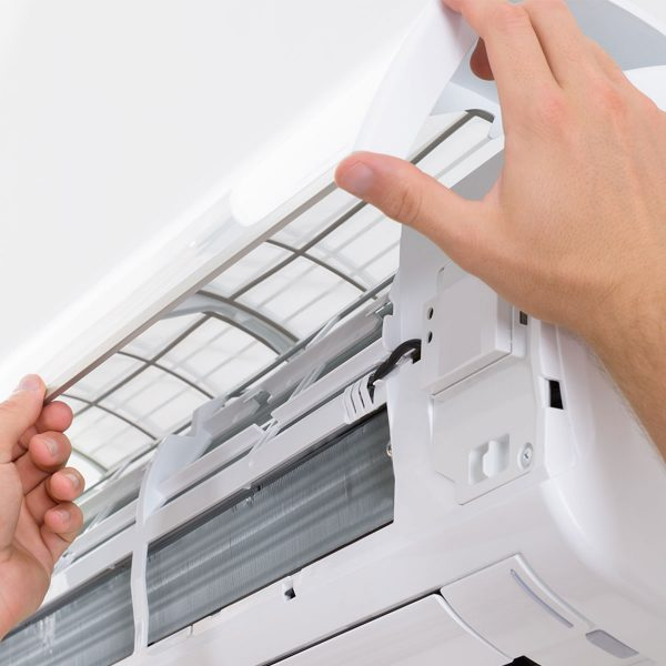 hands opening air conditioning unit to view insides