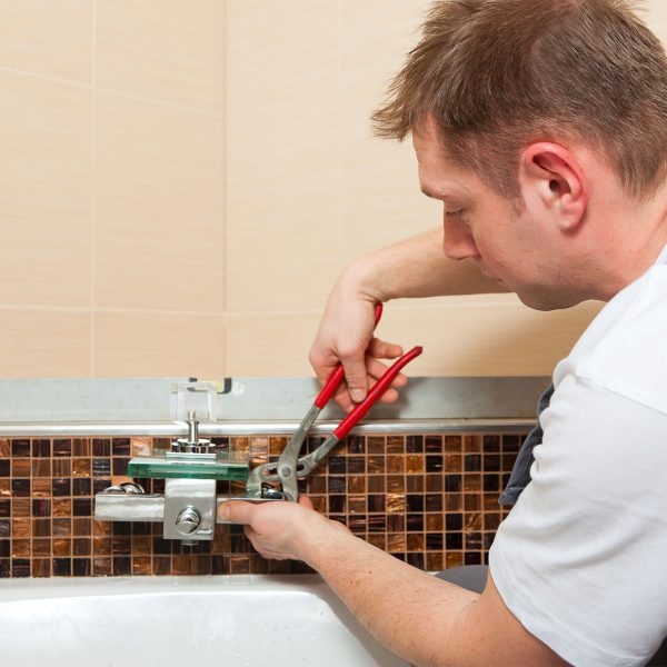 man fitting taps with wrench in bathroom