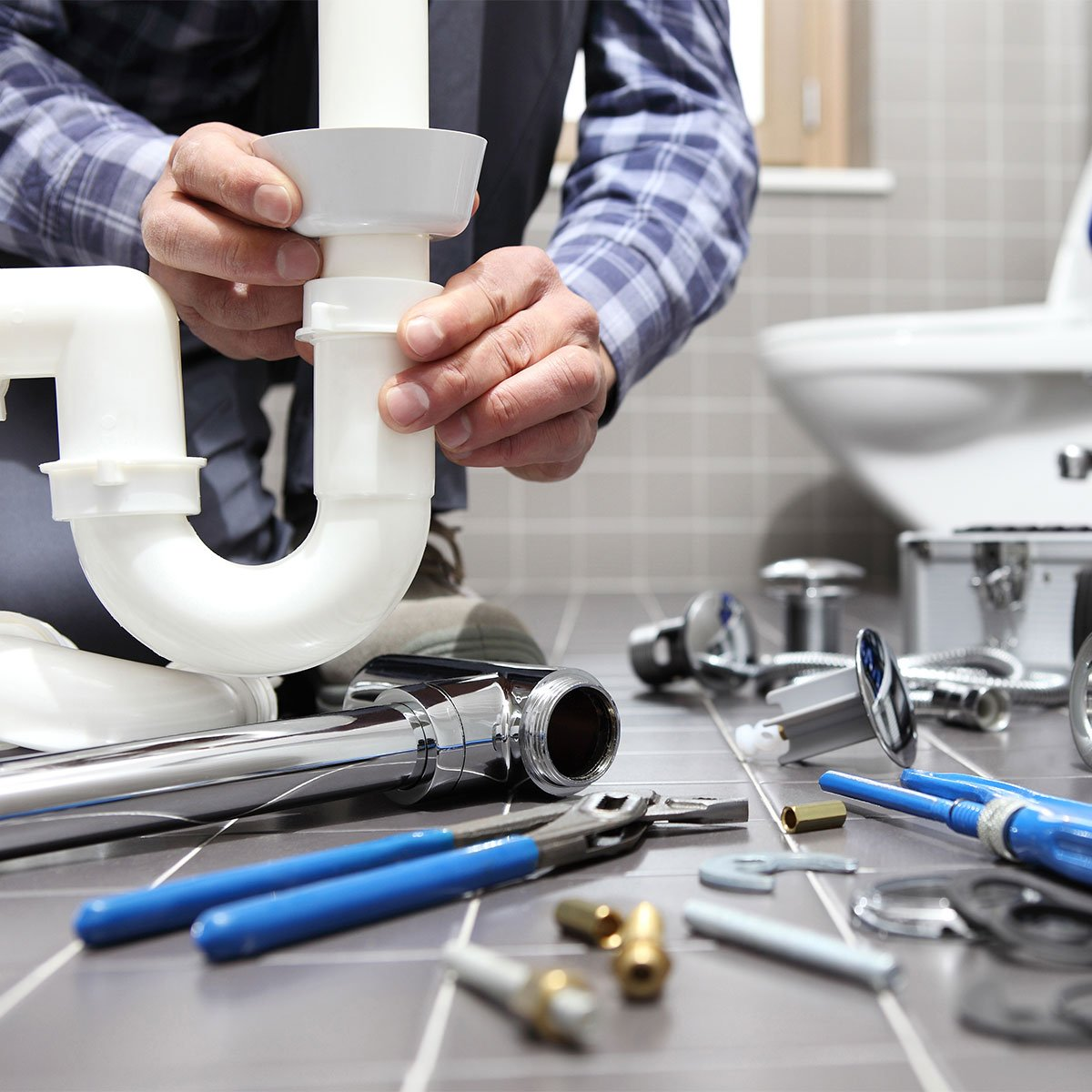 man in bathroom constructing pipes with several tools