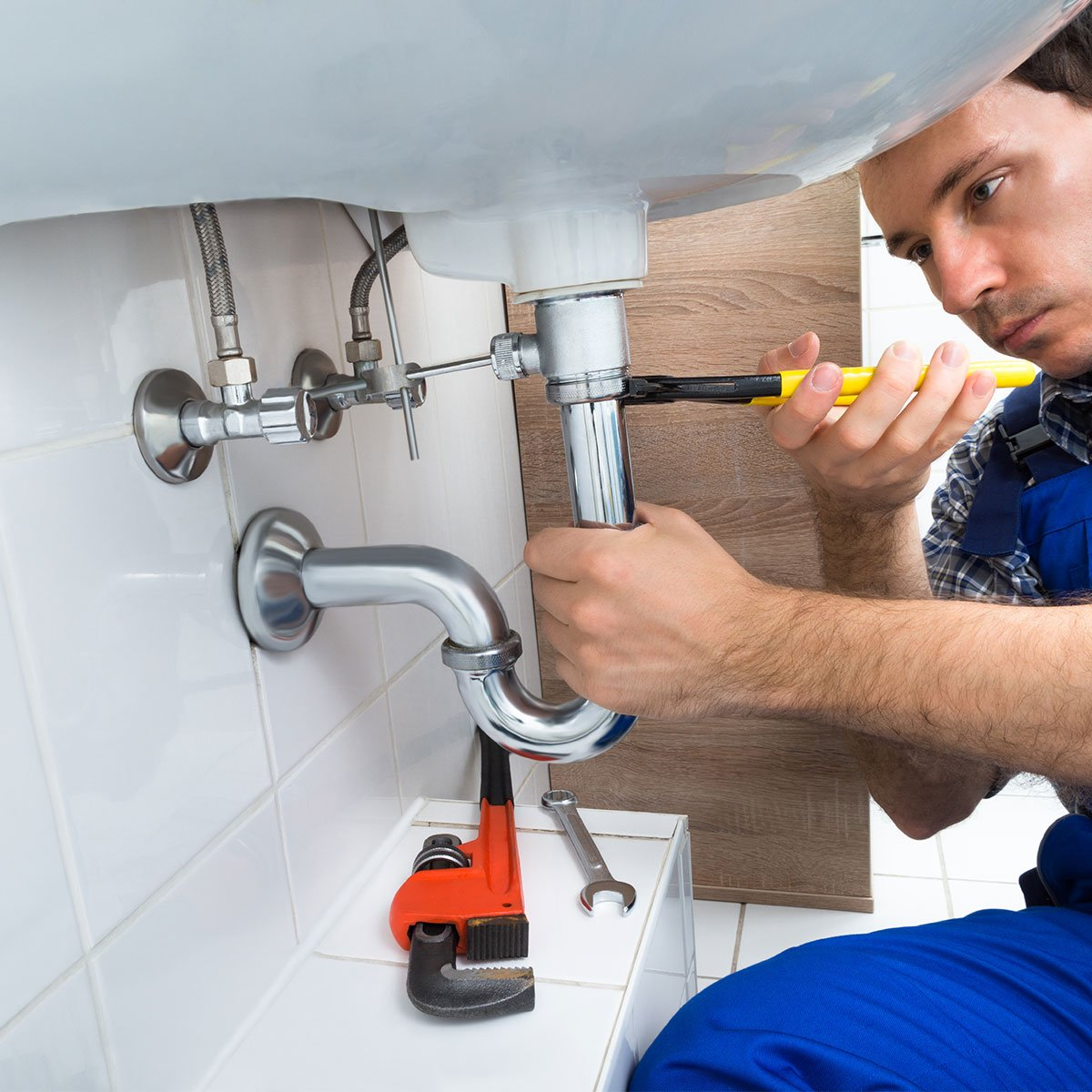man fitting pipes under sink