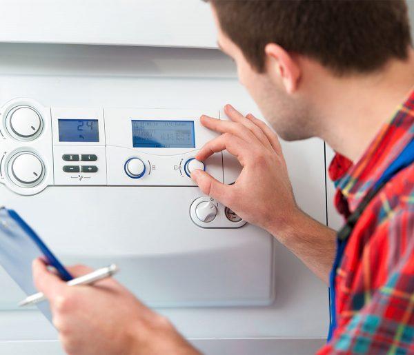 man adjusting controls on boiler