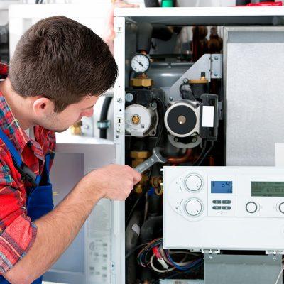 man fixing boiler with tool