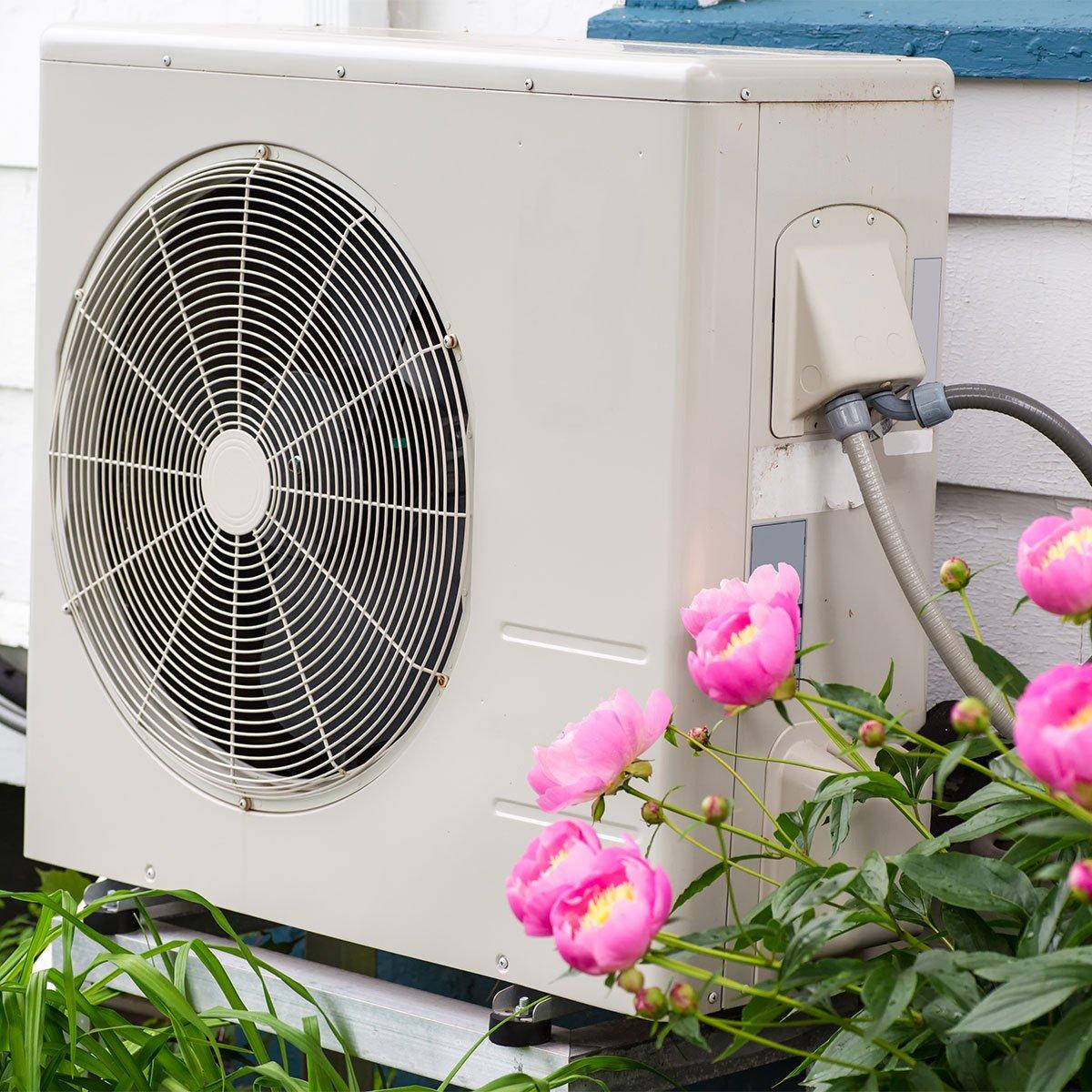 Outdoor heat pump in garden surrounded by flowers