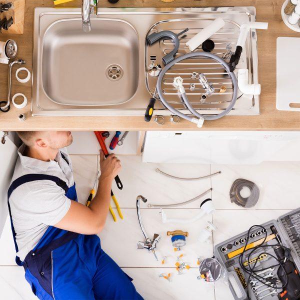 man plumbing under sink in kitchen