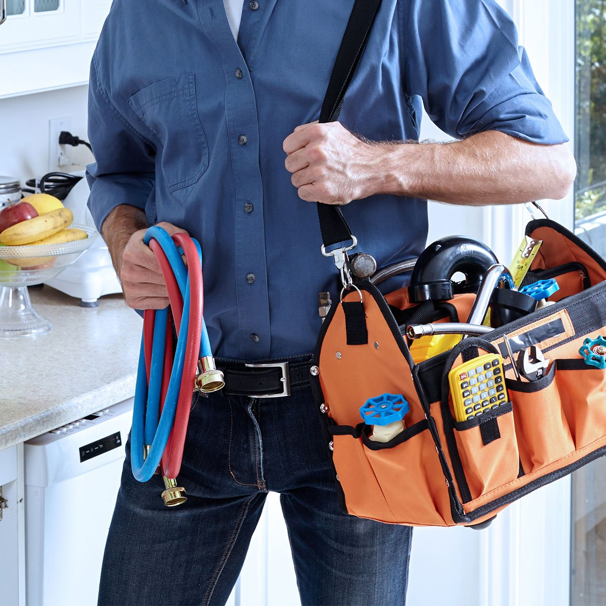 Plumber carrying plumbing tool kit and pipes