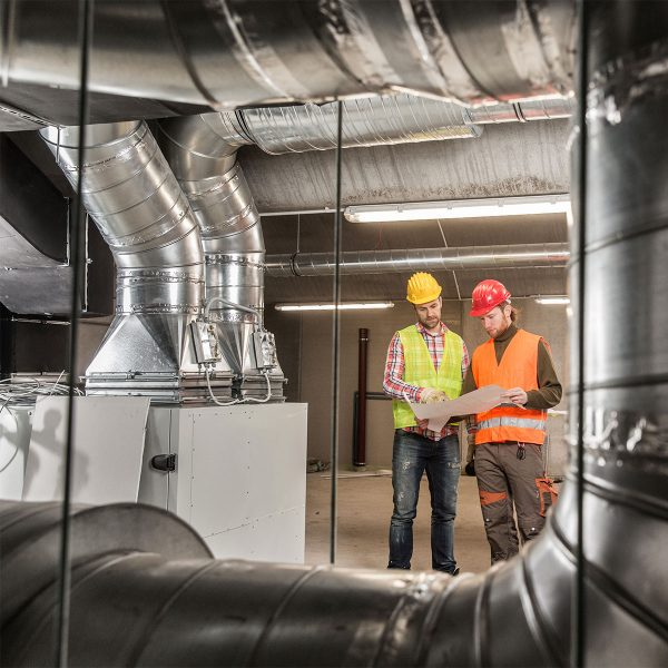 2 men in hi-vis jackets inspecting ventilation systems